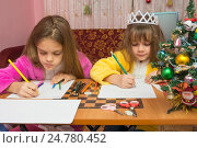 Купить «Две девочки пишут рождественские поздравительные письма сидя за столом в домашней обстановке», фото № 24780452, снято 25 декабря 2016 г. (c) Иванов Алексей / Фотобанк Лори