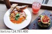 Купить «gazpacho soup, salad and drink at restaurant», видеоролик № 24781400, снято 29 сентября 2016 г. (c) Syda Productions / Фотобанк Лори