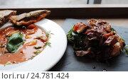 Купить «gazpacho soup, salads and drink at restaurant», видеоролик № 24781424, снято 29 сентября 2016 г. (c) Syda Productions / Фотобанк Лори