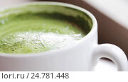 Купить «teaspoon stirring matcha green tea latte in cup», видеоролик № 24781448, снято 29 сентября 2016 г. (c) Syda Productions / Фотобанк Лори