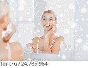 Купить «happy woman applying cream to face at bathroom», фото № 24785964, снято 13 февраля 2016 г. (c) Syda Productions / Фотобанк Лори