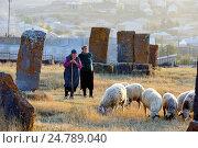 Купить «Shepherdess at Noratus cemetery (the largest surviving cemetery with khachkars in Armenia), near Lake Sevan, Gegharkunik region, Armenia, Eurasia.», фото № 24789040, снято 5 октября 2016 г. (c) age Fotostock / Фотобанк Лори