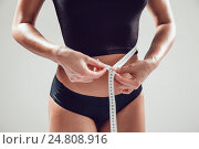 Athletic slim woman measuring her waist by measure tape on white background. Стоковое фото, фотограф Женя Канашкин / Фотобанк Лори