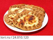 Купить «Калитки с картошкой в белой тарелке на красном фоне», фото № 24810120, снято 3 января 2017 г. (c) Наталья Осипова / Фотобанк Лори