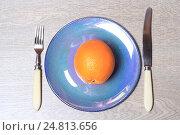 Купить «Апельсин на тарелке вилка и нож», эксклюзивное фото № 24813656, снято 5 января 2017 г. (c) Яна Королёва / Фотобанк Лори