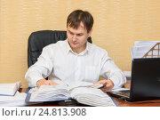 Купить «Мужчина в офисе за столом  смотрит в документы в папках», фото № 24813908, снято 4 января 2017 г. (c) Гетманец Инна / Фотобанк Лори