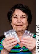 Пожилая женщина держит блистеры с таблетками улыбается и смотрит в кадр, фото № 24818780, снято 6 января 2017 г. (c) Эдуард Паравян / Фотобанк Лори