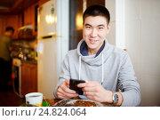 Купить «Позитивный молодой человек завтракает на кухне с телефоном в руках», фото № 24824064, снято 20 февраля 2016 г. (c) Евгений Майнагашев / Фотобанк Лори