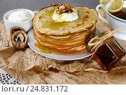 Купить «Блинчики с медом, сметаной и грецкими орехами на бумажной салфетке. Профессиональная студийная фотосъемка на сером каменном столе.», фото № 24831172, снято 24 марта 2019 г. (c) Olesya Tseytlin / Фотобанк Лори