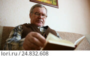 Old man sitting on the couch at home reading a book. Стоковое видео, видеограф Сергей Кальсин / Фотобанк Лори