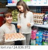 Купить «Happy Woman with little girl choosing selecting eggs», фото № 24836972, снято 23 января 2016 г. (c) Татьяна Яцевич / Фотобанк Лори
