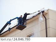 Купить «Рабочие скалывают опасный снежный карниз с крыши», эксклюзивное фото № 24846780, снято 29 декабря 2016 г. (c) Иван Карпов / Фотобанк Лори