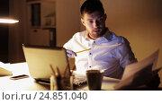 Купить «man with laptop and papers working at night office», видеоролик № 24851040, снято 4 декабря 2016 г. (c) Syda Productions / Фотобанк Лори