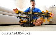 Купить «Kid plays with toy excavator from constructor», видеоролик № 24854072, снято 8 января 2017 г. (c) Володина Ольга / Фотобанк Лори