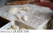 Купить «Grandmother cuts dough for pies», видеоролик № 24854104, снято 6 января 2017 г. (c) Володина Ольга / Фотобанк Лори