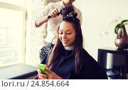 Купить «happy woman with stylist making hairdo at salon», фото № 24854664, снято 15 февраля 2015 г. (c) Syda Productions / Фотобанк Лори