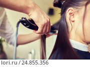 Купить «stylist with iron straightening hair at salon», фото № 24855356, снято 15 февраля 2015 г. (c) Syda Productions / Фотобанк Лори