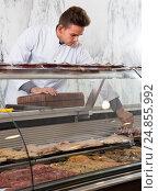 Купить «calm man cook cutting meat in butcher market», фото № 24855992, снято 20 октября 2016 г. (c) Яков Филимонов / Фотобанк Лори