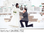Guy asks the girl hands. Winter wedding, groom on his knee in front of the bride a snowy street. The marriage concept , will you marry me. Стоковое фото, фотограф Евгений Майнагашев / Фотобанк Лори