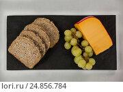Купить «Slices of brown bread, grapes and gouda cheese on slate board», фото № 24856784, снято 16 сентября 2016 г. (c) Wavebreak Media / Фотобанк Лори