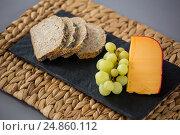 Купить «Gouda cheese, bread slices and grapes on slate plate», фото № 24860112, снято 16 сентября 2016 г. (c) Wavebreak Media / Фотобанк Лори