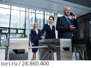 Купить «Businesspeople scanning their cards at turnstile gate», фото № 24860400, снято 6 июля 2016 г. (c) Wavebreak Media / Фотобанк Лори
