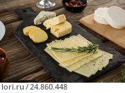 Купить «Variety of cheese and rosemary herbs on wooden table», фото № 24860448, снято 16 сентября 2016 г. (c) Wavebreak Media / Фотобанк Лори