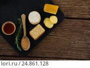 Купить «Cheese, crackers, nacho chips and rosemary herbs on slate plate», фото № 24861128, снято 16 сентября 2016 г. (c) Wavebreak Media / Фотобанк Лори