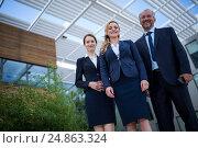 Купить «Confident businesspeople standing in the office premises», фото № 24863324, снято 6 июля 2016 г. (c) Wavebreak Media / Фотобанк Лори