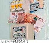 Купить «Электросчетчик и пятитысячная купюра», фото № 24864448, снято 7 января 2017 г. (c) Геннадий Соловьев / Фотобанк Лори