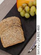 Купить «Slices of brown bread, grapes and gouda cheese on slate board», фото № 24865460, снято 16 сентября 2016 г. (c) Wavebreak Media / Фотобанк Лори
