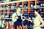 portrait of male seller showing bottle of wine to female custom, фото № 24866120, снято 15 января 2017 г. (c) Яков Филимонов / Фотобанк Лори