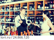 Купить «portrait of male seller showing bottle of wine to female custom», фото № 24866120, снято 21 октября 2018 г. (c) Яков Филимонов / Фотобанк Лори