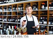 Купить «Man seller wearing uniform holding glass of wine», фото № 24866156, снято 17 июля 2018 г. (c) Яков Филимонов / Фотобанк Лори
