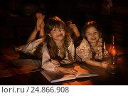 Купить «Девочки читают книгу на полу в избе», фото № 24866908, снято 25 февраля 2016 г. (c) Марина Володько / Фотобанк Лори