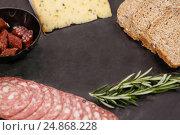 Купить «Brown bread, dutch gouda cheese, rosemary and meat on slate board», фото № 24868228, снято 16 сентября 2016 г. (c) Wavebreak Media / Фотобанк Лори