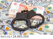 Купить «Черные стальные наручники лежат на пачке российских рублей на фоне американских долларов», фото № 24885004, снято 4 апреля 2020 г. (c) FotograFF / Фотобанк Лори