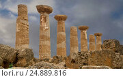 Купить «Remains of an ancient Greek temple of Heracles (V-VI century BC), Valley of the Temples, Agrigento, Sicily. The area was included in the UNESCO Heritage Site list in 1997», видеоролик № 24889816, снято 18 января 2017 г. (c) Владимир Журавлев / Фотобанк Лори
