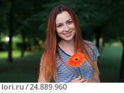 Young woman portrait. Simling girl with orange flower gerberas looking at camera. Outdoor natural portrait. Стоковое фото, фотограф Евгений Пидеркин / Фотобанк Лори