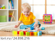 Купить «Child toddler playing toy blocks in his room or nursery», фото № 24898216, снято 26 декабря 2014 г. (c) Оксана Кузьмина / Фотобанк Лори