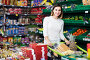 positive girl customer looking for tasty sweets in supermarket, фото № 24900336, снято 23 ноября 2016 г. (c) Яков Филимонов / Фотобанк Лори