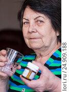 Пожилая женщина смотрит в камеру, держит в руках стакан с водой и флакон медикаментов, фото № 24909188, снято 6 января 2017 г. (c) Эдуард Паравян / Фотобанк Лори