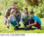 Купить «Young parents with two kids placing a new tree», фото № 24909940, снято 20 апреля 2018 г. (c) Яков Филимонов / Фотобанк Лори