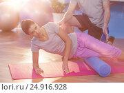 Купить «Low section of physiotherapist assisting woman while exercising on exercise mat», фото № 24916928, снято 8 декабря 2019 г. (c) Wavebreak Media / Фотобанк Лори
