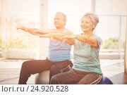 Купить «Happy senior couple performing exercise», фото № 24920528, снято 28 мая 2020 г. (c) Wavebreak Media / Фотобанк Лори