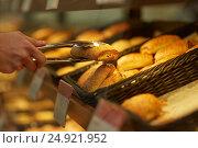 Купить «hand with tongs taking bun at bakery or grocery», фото № 24921952, снято 2 ноября 2016 г. (c) Syda Productions / Фотобанк Лори