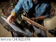 Купить «man with guitar writing to music book at studio», фото № 24922076, снято 18 августа 2016 г. (c) Syda Productions / Фотобанк Лори