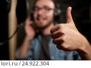 Купить «singer showing thumbs up at sound recording studio», фото № 24922304, снято 18 августа 2016 г. (c) Syda Productions / Фотобанк Лори