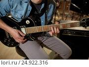 Купить «man playing guitar at studio rehearsal», фото № 24922316, снято 18 августа 2016 г. (c) Syda Productions / Фотобанк Лори