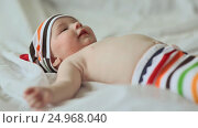 Купить «Funny four month old baby lying on his back and smiling. Dressed baby in striped shorts and cap», видеоролик № 24968040, снято 20 января 2017 г. (c) Mikhail Davidovich / Фотобанк Лори